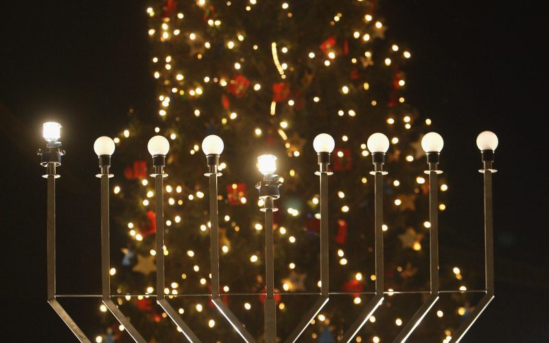 BERLIN - DECEMBER 04: A giant, gas-lit menorah stands in front of a Christmas tree shortly after members of the local Jewish community lit the menorah on the night before the first day of Hannukah December 4, 2007 in Berlin, Germany. Berlin's Jewish community has grown sharply in recent years with the arrival of thousands of Jews from the former Soviet Union. (Photo by Sean Gallup/Getty Images)